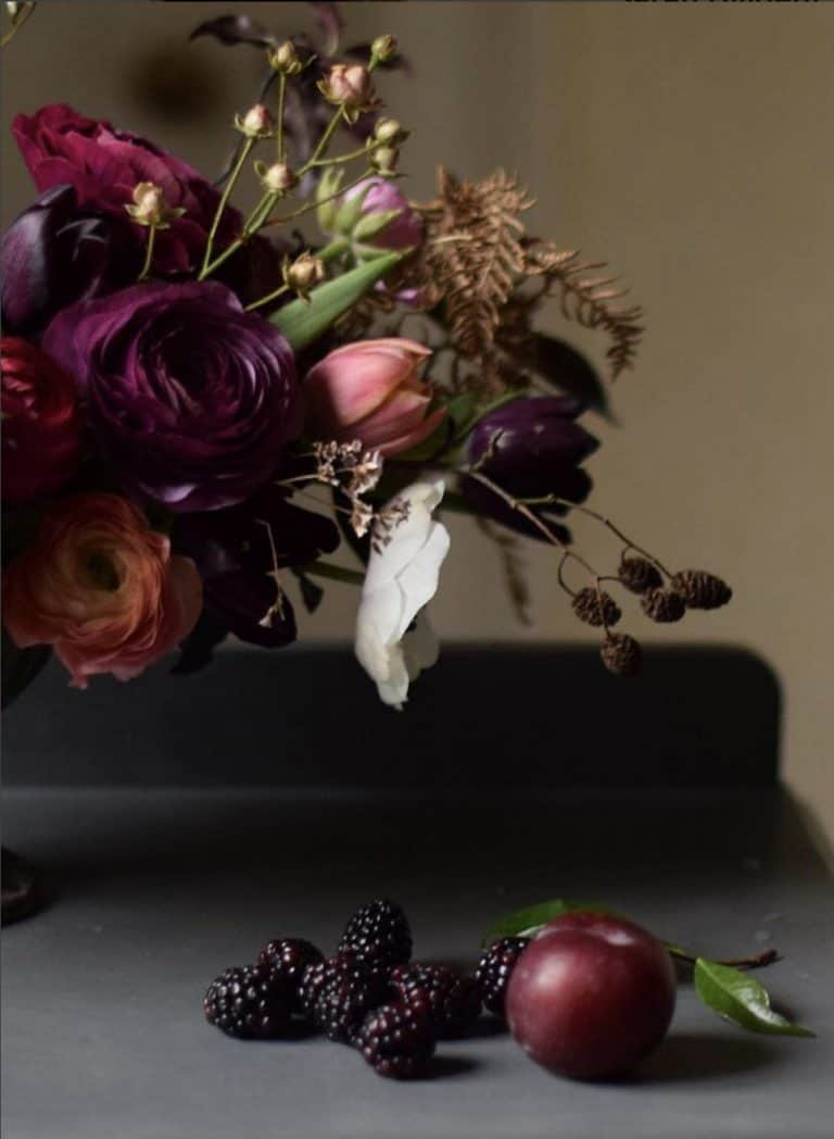 love this autumn flower arrangement by Sarah Diligent of Floribunda Rose using british flowers including jewel shade ranunculus, tulips, anemone, blackberries, seed heads, ferns, autumn leaves, foraged foliage and seasonal berries and greenery. Click through for more autumn flower arrangement ideas you