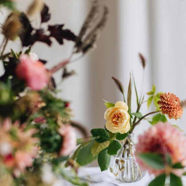 simple jam jar flowers for autumn. click through for more seasonal flower ideas and step by steps to create seasonal simple flower arrangements using autumn blooms including dahlias, dried flowers, herbs and foliage #autumn #flowers #britishflowers